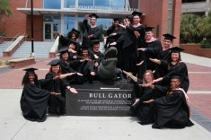 masters students doing gator chomp in front of bull gator statue